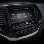 The in-dash head unit of the 2015 Jeep Cherokee includes features such as navigation and stereo controls.