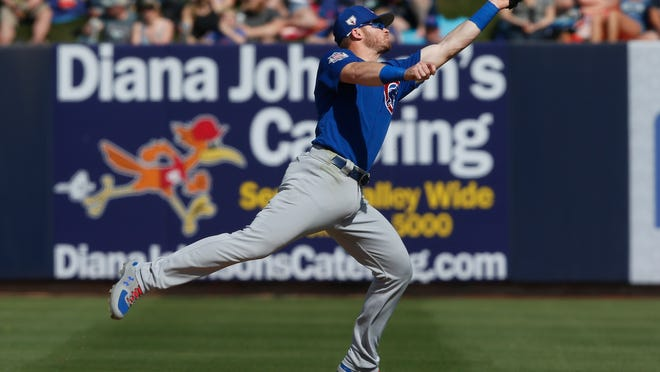 Chicago Cubs' second baseman Ian Happ reaches for a fly ball hit by Milwaukee Brewers' Cory Spangenberg for an out in the fifth inning of a spring training baseball game Sunday, March 10, 2019, in Phoenix. (AP Photo/Sue Ogrocki)