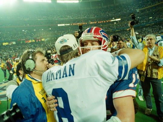Dallas Cowboys' winning quarterback Troy Aikman embraces Buffalo Bills' quarterback Jim Kelly after the Cowboys' 30-13 Super Bowl win.