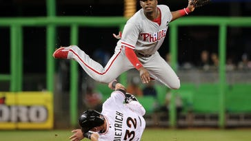 Phillies second baseman Darnell Sweeney turns a double play as Marlins left fielder Derek Dietrich slides into second base on Wednesday.