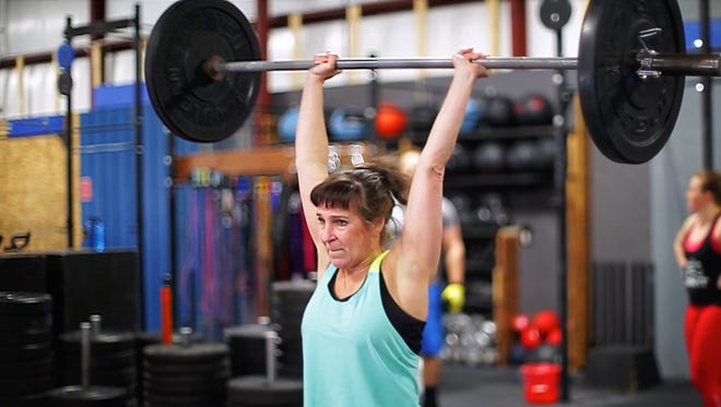 Denise Ristow, 62, of Sheboygan, lifts weights during her competition routine at Crossfit Eastern Ridge, Saturday, April 21, 2018, in Sheboygan, Wis.  Ristow is in the top 200 for the Crossfit Games.