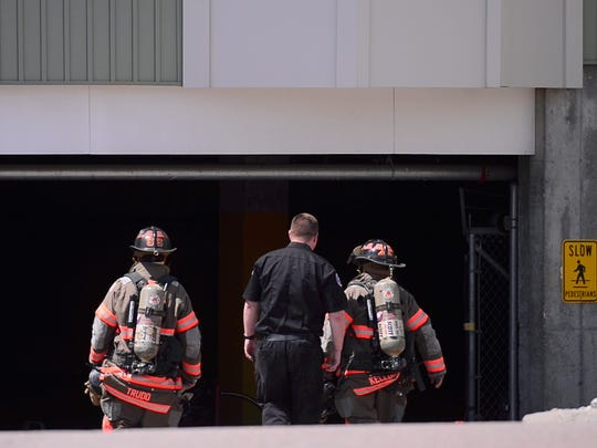 Firefighters inspect the garage area at Mansfield Place at 18 Carmichael Street in Essex after carbon monoxide alarms went off, triggering an evacuation and response for multiple fire agencies and ambulance crews on Tuesday, May 1, 2018. Four people were transported to the hospital.