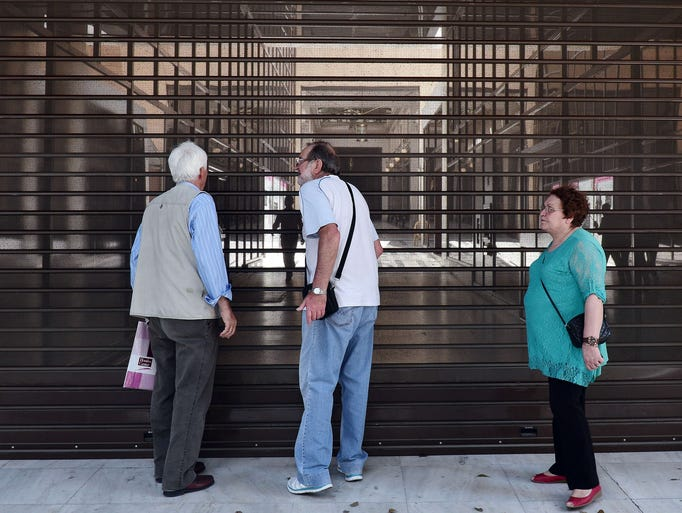 Pensioners stand behind shutters of the Alpha Bank