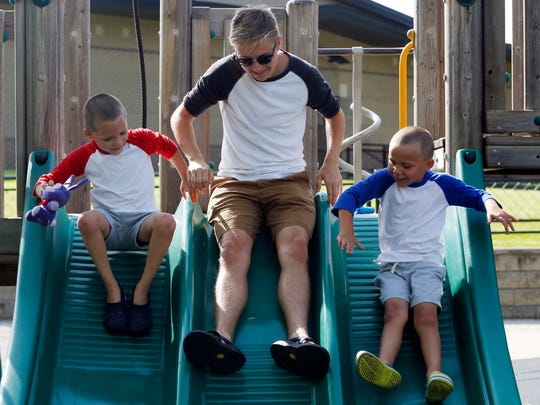 Ben Christiason goes down the slide with twin brothers Lincoln (left) and Ashton Zars, 5, Wednesday, July 13, 2016, in Cedar Falls. Christiason is working as a nanny for the Zars family as he gets ready to head off to college this fall.
