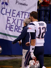New England Patriots quarterback Tom Brady (12) walks past a sign referencing Deflategate at halftime during the NFL game against the Indianapolis Colts at Lucas Oil Stadium.