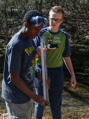 Jacoby Smith, 13, left, and Hunter Caruthers, 12, students at Reed Academy, test the turbidity of the water, which measures a liquids cloudiness, during a field trip at the Watershed Center on Monday, Feb. 27, 2017.