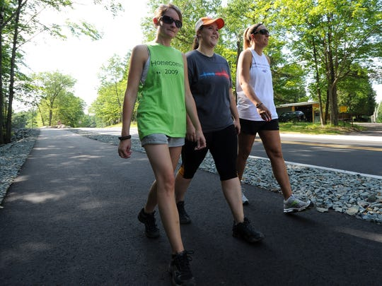 People walk on the paved pathway alongside the road leading to Rib Mountain State Park.