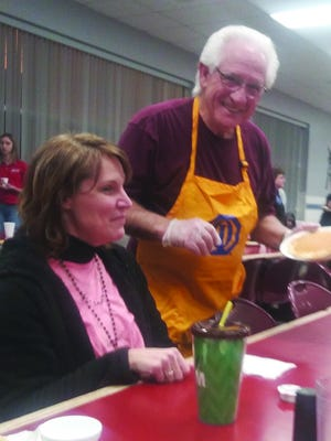 Richard Drake, Pratt Optimist Club member, offers more pancakes to Kim Staats at the club's annual pancake and sausage dinner last week.