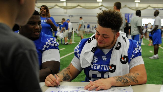 Nose guard Matt Elam signs a poster during the UK football fan day in Lexington, Ky., on Saturday, Aug. 6, 2016.