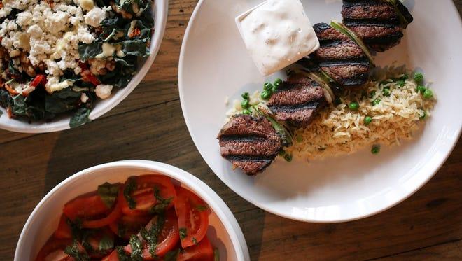 Steak skewers with tzatziki and basmati rice, alongside vegetables and salad at Char Kitchen + Bar.