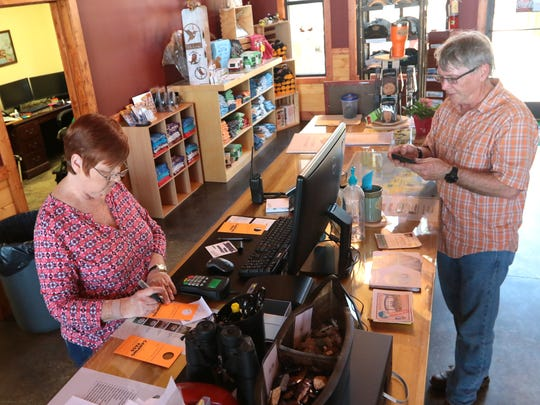 Mandy Holbrooks, left, helps Jonathan Bartley of Georgia checking in at the front office at South Cove County Park in Seneca on Tuesday.