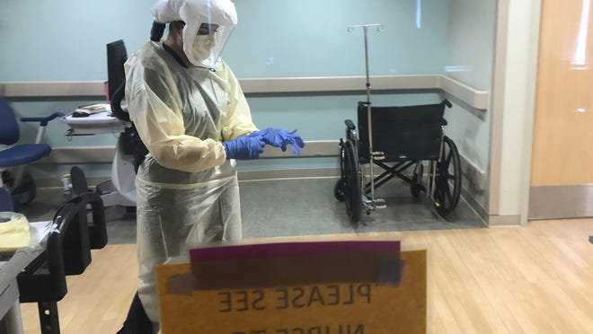 Dr. Ruba Nicola, chairwoman of family medicine at UPMC East, adjusts her personal protective equipment at the UPMC East hospital in Monroeville, Pa., on April 17, 2020. The University of Pittsburgh Medical Center's 40 hospitals in Pennsylvania, New York, Maryland and Ohio joined a study underway in the United Kingdom, Australia and New Zealand that randomly assigns patients to one of dozens of possible treatments and uses artificial intelligence to adapt treatments, based on the results.