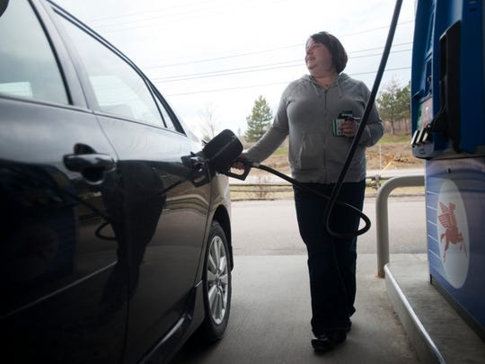 Jennifer Huyler of Milton pumps gas into her car at Maplefields gas station in Colchester last year.
