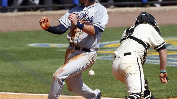 Mississippi's Preston Overbey (1) gets past Vanderbilt's Jason Delay (5) as he drops the ball to score during the third inning at the Southeastern Conference NCAA college baseball tournament on Thursday, May 22, 2014, in Hoover, Ala. (AP Photo/Butch Dill)