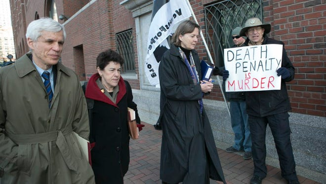 Dzhokhar Tsarnaev's defense attorneys pass anti-death penalty protesters outside the court in Boston on Wednesday.