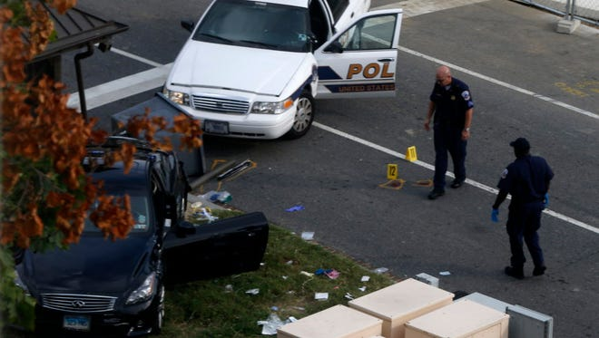 Capitol Hill police officers looking at a car after a  chase and shooting in 2013.