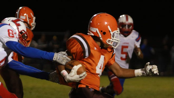 Adrian McCoy of Heath runs with the ball while Lakewood tries to tackle him. The Heath Bulldogs hosted the Lakewood Lancers Friday night. Heath took the win 53-27.