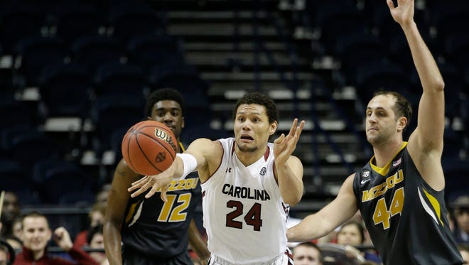 South Carolina forward Michael Carrera (24) moves the ball as Missouri forward Ryan Rosburg (44) and Missouri guard Namon Wright (12) look on during the second half of an NCAA college basketball game in the first round of the Southeastern Conference tournament, Wednesday, March 11, 2015, in Nashville, Tenn.