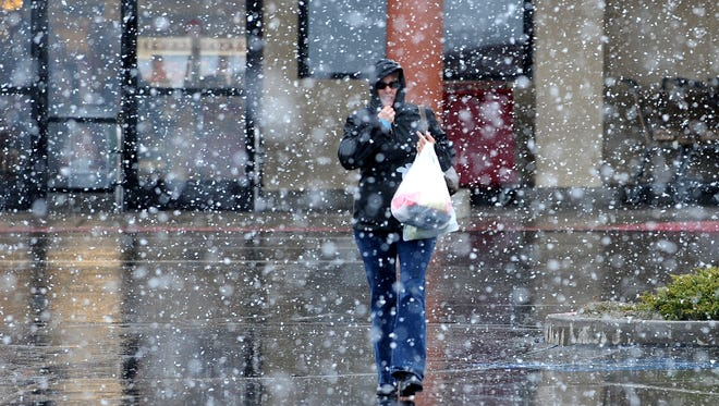 A file photo of a woman walking through rain and snow in Reno. Forecasters predict back-to-back storms to hit the Sierra, dropping rain and snow and blasting high winds through the weekend and into early next week.