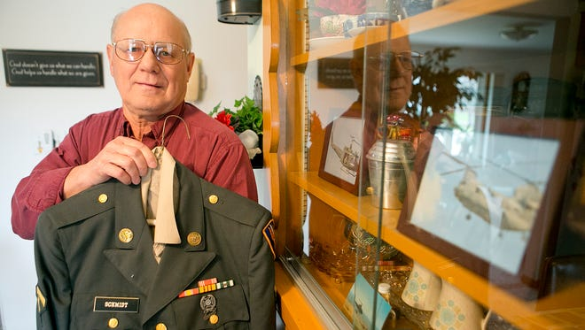 Ken Schmidt displays the uniform he wore in Vietnam at his home in Loyal, Wednesday, April 22, 2015. In his cabinet are photos of a UH-1 helicopter and a CH-46 helicopter. During the war, Schmidt worked on both types of helicopter.