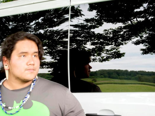 Last Bear Wilnoty leans against a van as a Native American