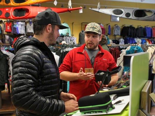Sales associate Bobby Fisk, right, shows the features