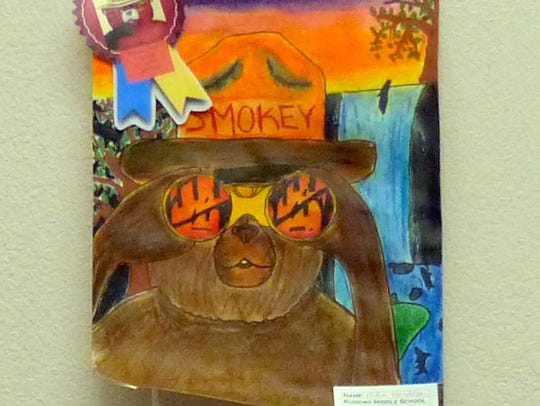 In this Ruidoso Middle School winner, Smokey Bear peers