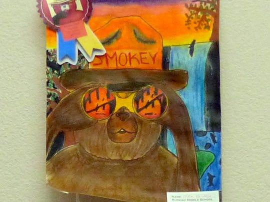 In this Ruidoso Middle School winner, Smokey Bear peers through binoculars at a wildfire.