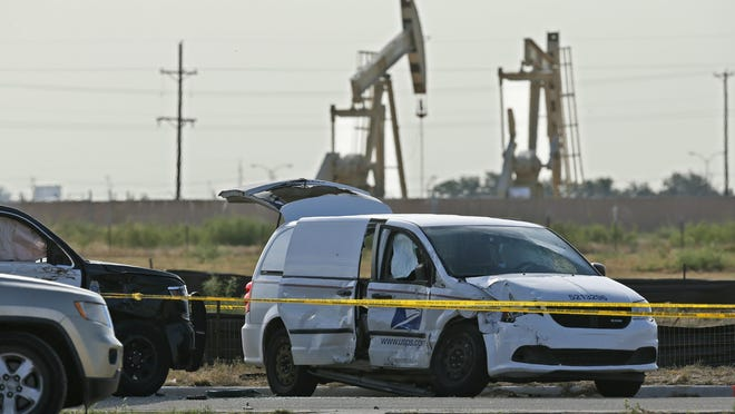 A U.S. Mail vehicle, right, which was involved in Saturday's shooting, is pictured outside the Cinergy entertainment center Sunday, Sept. 1, 2019, in Odessa, Texas. The death toll in the West Texas shooting rampage increased Sunday as authorities investigated why a man stopped by state troopers for failing to signal a left turn opened fire on them and fled, shooting over a dozen people as he drove before being killed by officers outside a movie theater. A police vehicle is partially blocked at left.