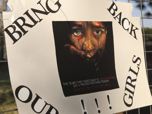 A poster on a Johannesburg school fence calls for the release of the kidnapped girls in Nigeria, Tuesday, May 13, 2014. Boko Haram, the militant group that is holding some 276 female students it kidnapped last month from a boarding school in northeast Nigeria, said the girls will only be freed after the government releases jailed militants. (AP Photo/Denis Farrell)