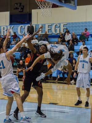 Ventura College sophomore Vida Faniel is corralled by Moorpark College's Nicholas Beccera (21) and Larry Williams during the Raiders' 77-76 upset win over the Pirates during the regular season.