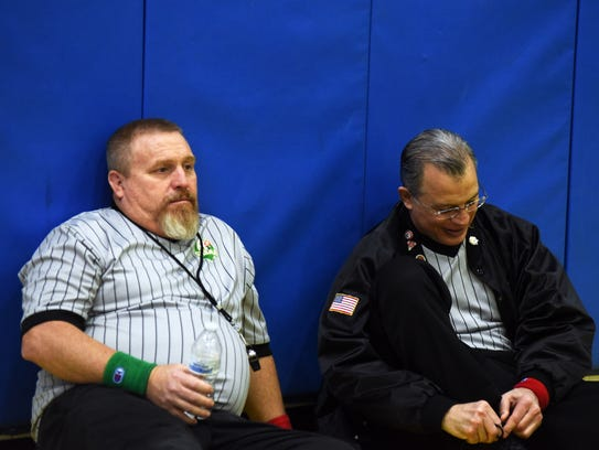 Officials Craig Clarke, left, and Don Mason take in