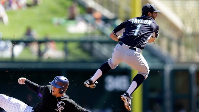 Seattle Mariners' Chris Taylor hops over Colorado Rockies' Brandon Barnes to complete a double play in the first inning of a spring training exhibition baseball game Tuesday, March 10, 2015, in Scottsdale, Ariz. Rockies' Carlos Gonzalez was out at first base.