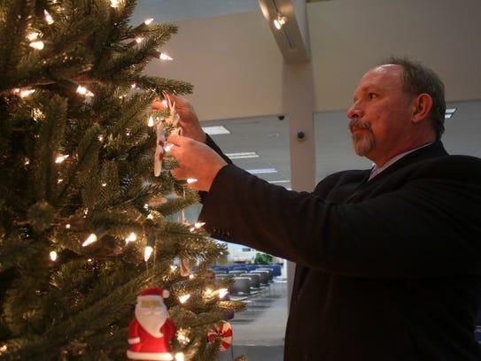 Assistant District Attorney Robert Nash hangs an ornament