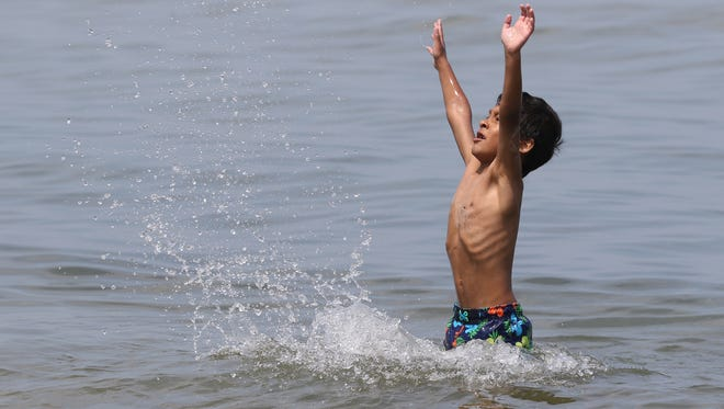 Anthony Diaz, 7, of Irondequoit plays in Lake Ontario at Ontario Beach Park with his cousin on Saturday.
