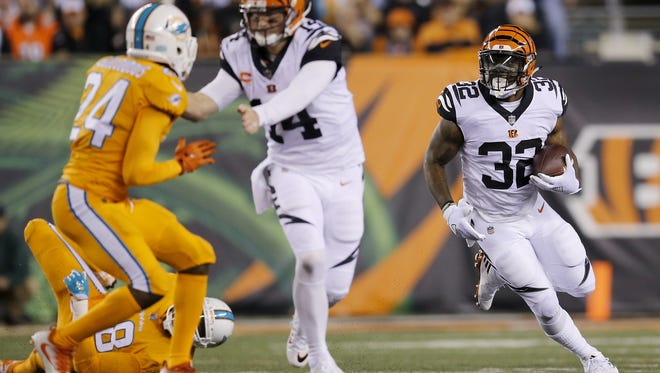 Cincinnati Bengals running back Jeremy Hill (32) breaks to the outside with a block from quarterback Andy Dalton (14) in the second quarter of the NFL Week 4 game between the Cincinnati Bengals and the Miami Dolphins at Paul Brown Stadium on Thursday, Sept. 29, 2016. At halftime the Bengals lead 16-7.