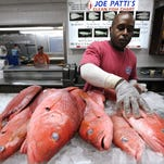 Terrance Williams of Joe Patti's Seafood in Pensacola, Fla., stocks a display cooler with red snapper on Tuesday, Sept. 4, 2012.