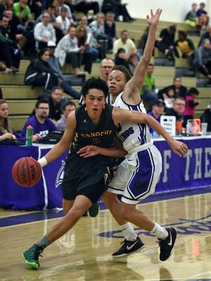 Spanish Springs' Kevonne Augustus covers Bishop Manogue's Brevon Bansuelo as he drives to the basketball during Tuesday's game at Spanish Springs