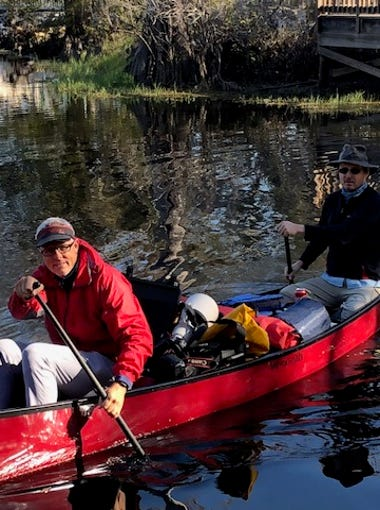 """News-Press photographer Andrew West and reporter Chad Gillis paddle their canoe at the start of the Kissimmee River near Orlando on Jan. 31, 2018. They are embarking on a 10-journey that will end at Lake Okeechobee. They are working on a special report called """"State of Water."""""""