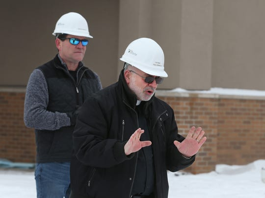 Father Paul Bonacci, right, leads spectators and workers in a prayer before crews install the large cross atop St. Pius Church in Chili on Friday, Dec. 15, 2017.  The church was badly damaged by a fire on New Year's Day 2015.