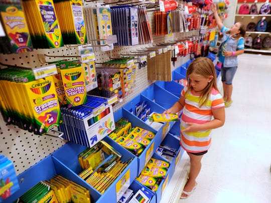 A pair of sisters pick out various items while shopping for school supplies in this 2013 file photo. Consumers will not be charged sales tax on many school items this weekend.