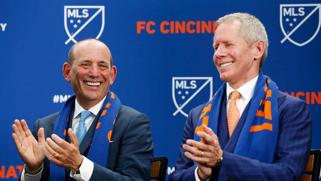 Major League Soccer commissioner Don Garber (left) and FC Cincinnati team owner Carl Lindner III smile during a speech made by mayor John Cranley at Rhinegeist Brewery in the Over-the-Rhine neighborhood of Cincinnati on Tuesday, May 29, 2018. FC Cincinnati was announced as the newest expansion team to join Major League Soccer.