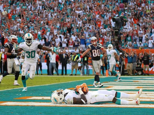 Michael Thomas of the Miami Dolphins celebrates a game-clinching interception in the end zone against the New England Patriots. Thomas picked off Tom Brady with 2 seconds remaining.