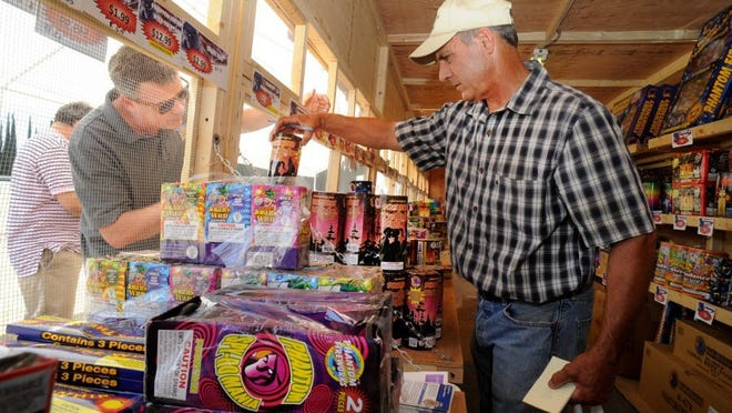JOSEPH A. GARCIA/THE STAR Joe Ricards (right), who teaches agriculture and is FFA adviser at Fillmore High, shows fireworks on Wednesday to Andrew Rankin, of Woodland Hills, who is one of the owners of Nova Storage that recently opened in Fillmore.