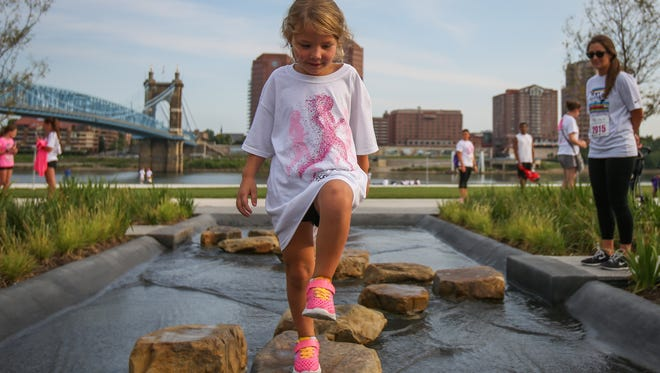 Survivors and supporters of breast cancer participated in the 18th annual Greater Cincinnati Susan G. Komen Race for the Cure. Ava Boyer, 4, jumps across stepping stones in Smale Park before the 5K.