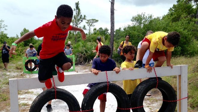 Seven-year old Christopher, in red, from Indian Harbour Beach jumps from one of the obstacles along the one-mile course during the Superhero Kids Club event at Wickham Park Sunday.