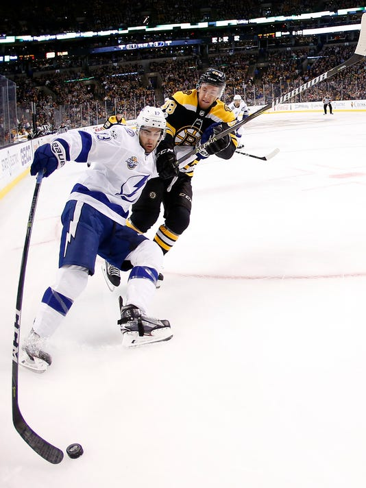 Tampa Bay Lightning's Cedric Paquette tries to hold off Boston Bruins' Matt Grzelcyk during the first period of an NHL hockey game in Boston Wednesday, Nov. 29, 2017. (AP Photo/Winslow Townson)