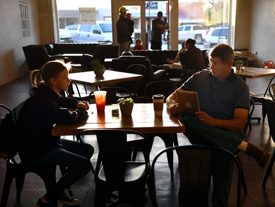 Jay Gage helps his daughter Brylie, 12, study for her sixth-grade science test Friday at Stomping Grounds Coffee & Tea Co. in Throckmorton. The donation-only coffee shop has been open since September.