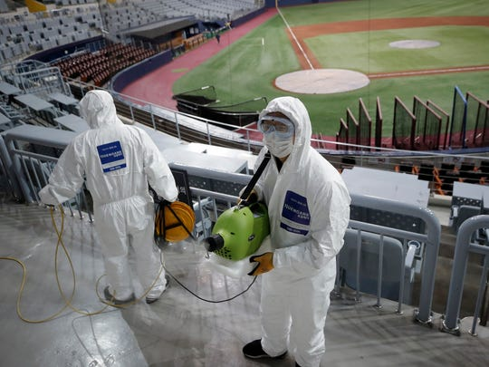 Workers wearing protective gear disinfect Gocheok Sky Dome in Seoul, South Korea, on March 17.