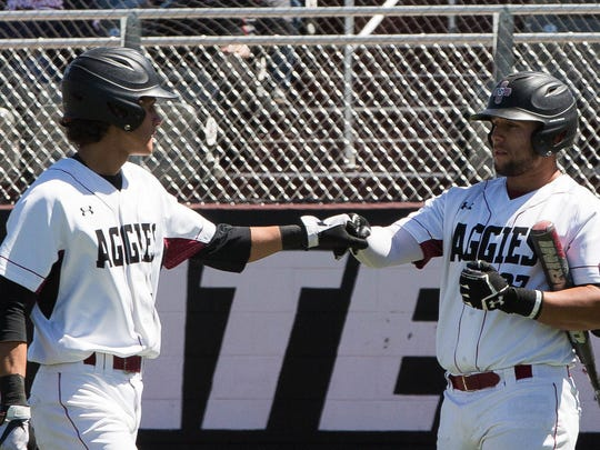 New Mexico State players Joey Ortiz, left, and Tristen Carranza fist bump after Ortiz crossed the plate against No. 6 Texas Tech on Tuesday at Presley Askew Field.